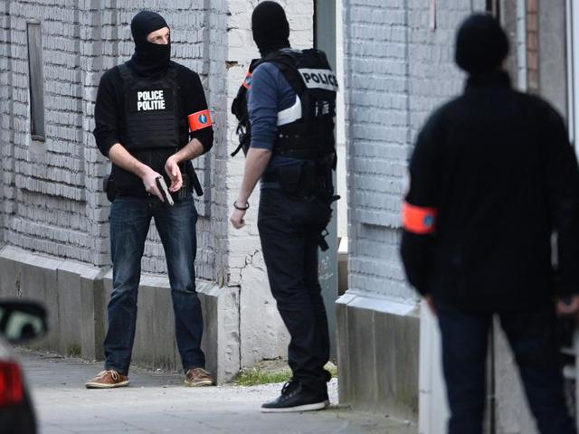 Police officers take position at the site of a shooting in the southern Forest district of Brussels.