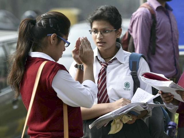 Class 12th students discuss their paper at an exam centre in New Delhi.