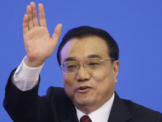 China's Premier Li Keqiang gestures at the end of a news conference following the closing ceremony of the National People's Congress (NPC) at the Great Hall of the People in Beijing.