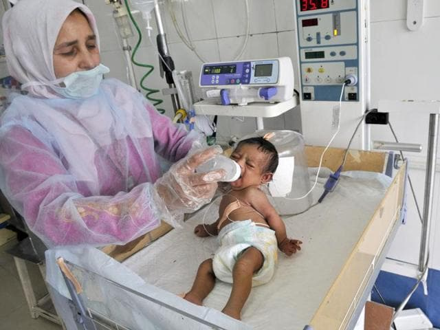 A nurse feeds a baby girl suffering from Down's Syndrome at Srinagar's GP Pant Hospital.