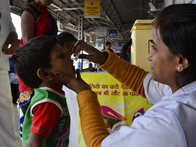 A health worker administers polio drops to a kid at a railway station in Bhopal.