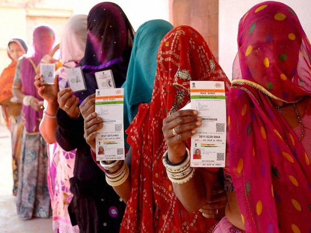 File photo of  Rajasthani women showing their respective Aadhaar cards while standing in a queue to vote for Ajmer District Panchayat elections on Friday.