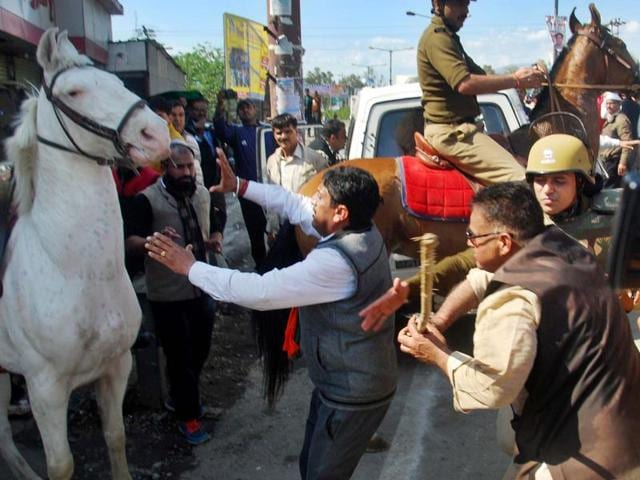 MLA Ganesh Joshi beating a police horse Shaktiman during a BJP rally at state assembly in Dehradun on Monday.