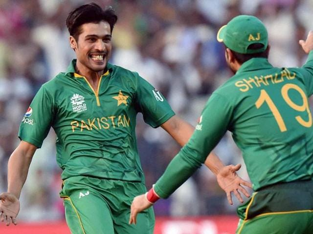 Pakistani bowler Mohammad Amir  celebrates with his team-mate Shahzad after taking a wicket.