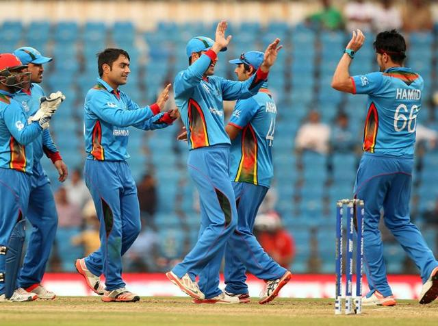 Rashid Khan of Afganistan celebrates the wicket of Vusi Sibanda with teammates during the T20 World Cup.