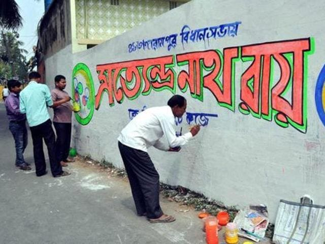 An artist makes graffiti for a Trinamool Congress (TMC) candidate ahead of the assembly elections at Balurghat, in South Dinajpur district of West Bengal.