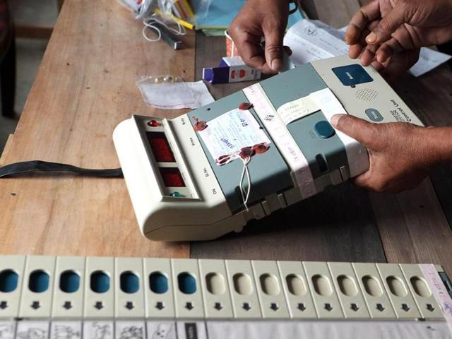Election Commission officials seal an Electronic Voting Machine (EVM) prior to the start of voting at a polling station in Dibrugarh, Assam. The EC has withdrawn its expenditure observer after an unauthorised raid was conducted.