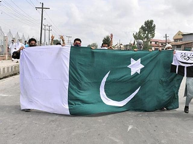 Masked protesters carrying a large Pakistan flag on the street in Jammu and Kashmir.
