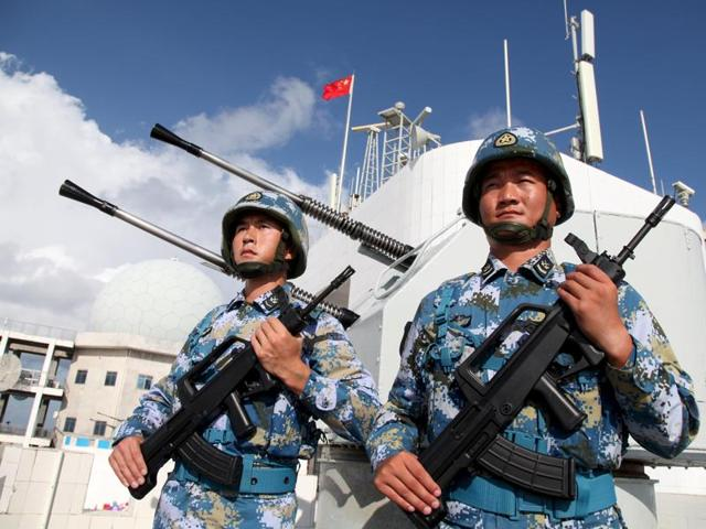 Chinese PLA soldiers stand guard at a warship in Beijing. Pakistan has rejected reports of PLA troops being sighted in Pakistan-occupied Kashmir.