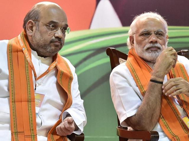 Prime Minister Narendra Modi talks with BJP president Amit Shah at party's National Executive meet, in New Delhi on Saturday.