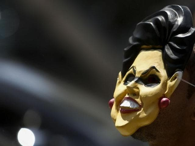 A demonstrator wearing a mask of Brazilian President Dilma Rousseff rallies in support of her impeachment at Paulista Avenue, in Sao Paulo, Brazil.