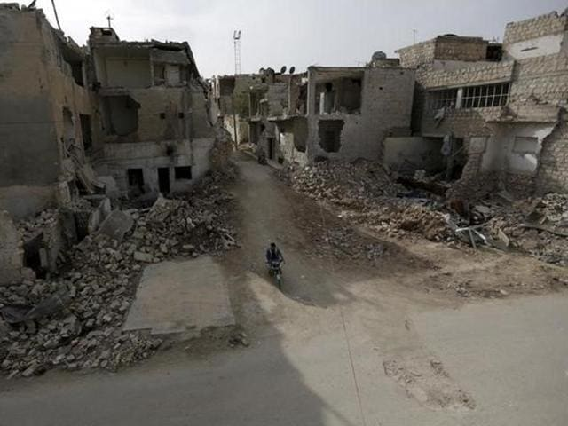A man rides a motorbike near damaged buildings in the town of Marat Numan in Idlib province, Syria.