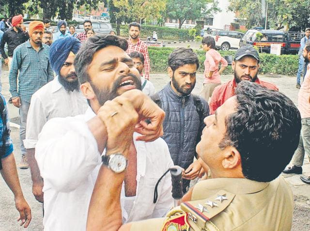 A cop trying to disperse students protesting on the Panjab University campus.