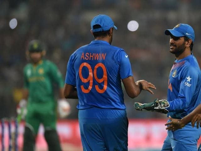 India's captain Mahendra Singh Dhoni(C)celebrates with teammates Ravichandran Ashwin(L)and Jasprit Bumrah(R)after Ashwin took a catch to dismiss Pakistan batsman Shoaib Malik during the World T20 cricket tournament.