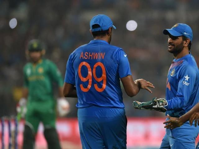India's captain Mahendra Singh Dhoni(C)celebrates with teammates Ravichandran Ashwin(L)and Jasprit Bumrah(R)after Ashwin took a catch to dismiss Pakistan batsman Shoaib Malik during the World T20 cricket tournament.