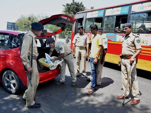 Police check a vehicle after a high alert was announced in Ahmedabad on Sunday.