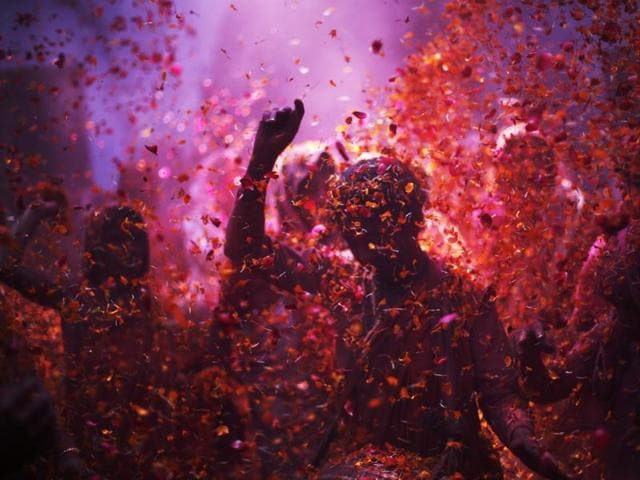 Widow daubed in colours dance as they take part in the Holi celebrations at Vrindavan.
