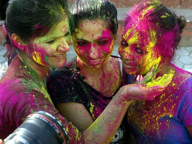 Young girls smear the faces of their friends with vibrant colors ahead of Holi, in Bhopal on Wednesday. (Bidesh Manna/HT photo)