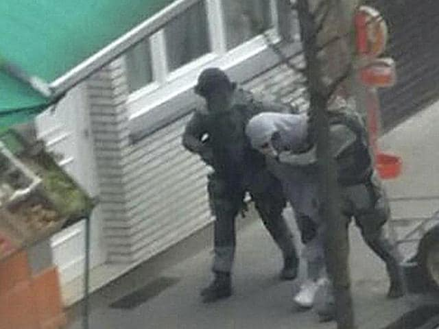 An unidentified man believed to be connected to key suspect in the November 2015 Paris attacks Salah Abdeslam, is detained by police during a raid in the Molenbeek neighborhood of Brussels, Belgium.