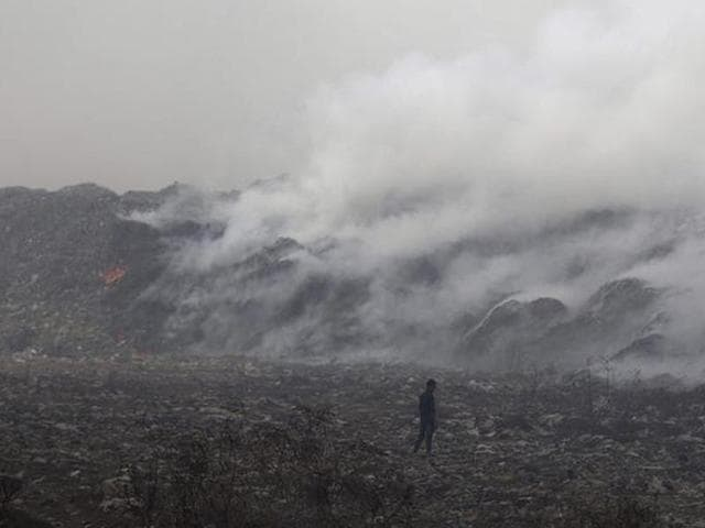 A rag picker collects recyclable material as smoke billows from the burning garbage at the Deonar dumping ground in Mumbai.
