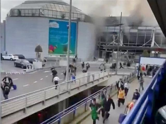 Passengers evacuate the Brussels Airport, in Zaventem, after a string of explosions rocked Brussels airport and a city metro station.