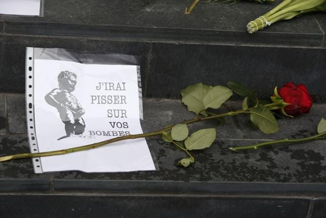 Floral tributes for the victims of Brussels attacks, including a picture of the Manneken Pis sculpture in Brussels, are placed on the steps of the Belgian embassy in Berlin, Germany.