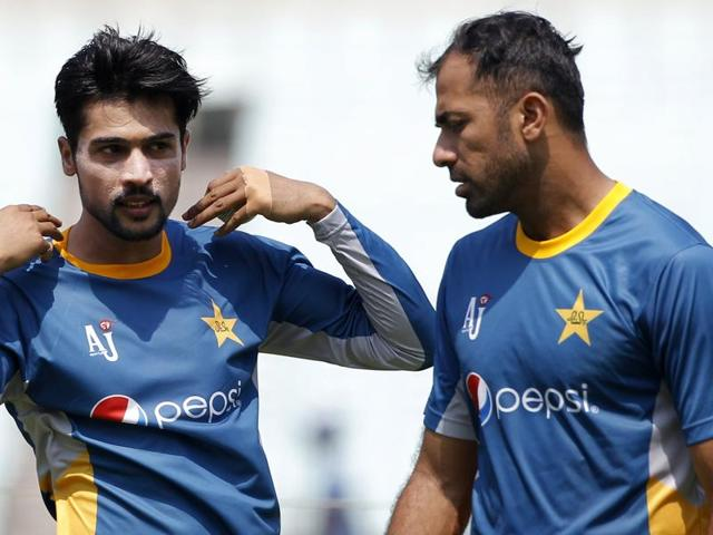 Pakistan's Mohammad Amir talks with Wahab Riaz during a training session prior to their match against Bangladesh.
