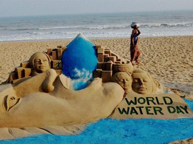 A woman carries water pot past sand sculpture of artist Manash Sahoo on the eve of World Water Day on Puri beach.