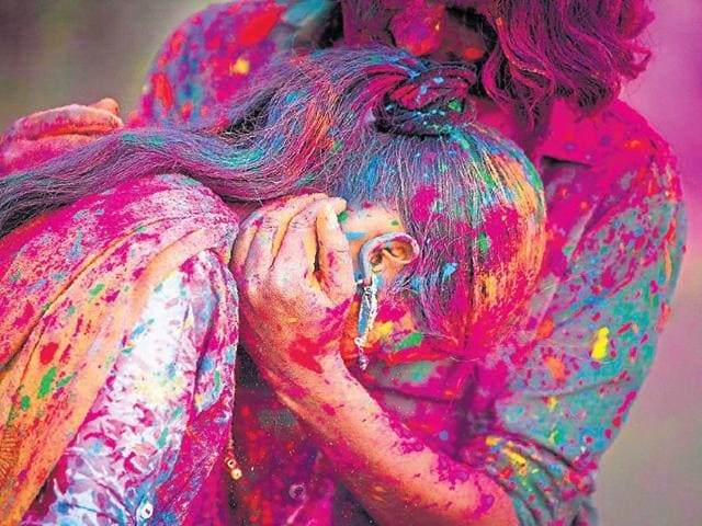 A girl gets smeared with colour during Holi celebrations.