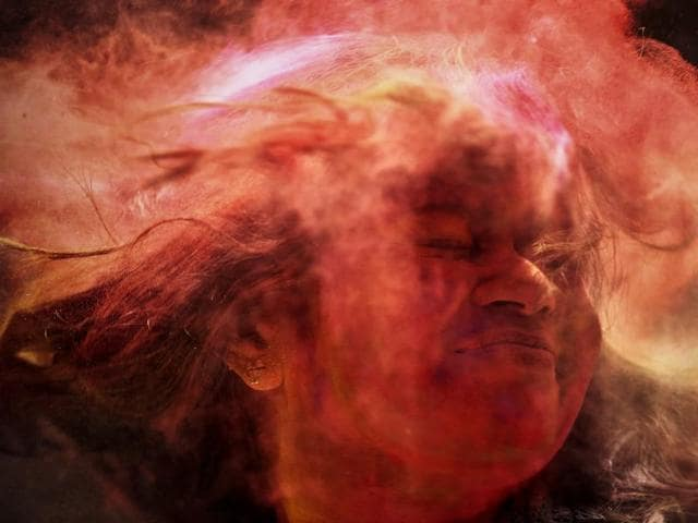 A woman shuts her eyes as coloured powder is smeared on her face during celebrations marking Holi..