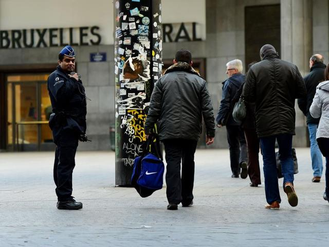 A Belgian police officer looks on as people walk past during an operation to limit the number of people allowed into the central station in Brussels.