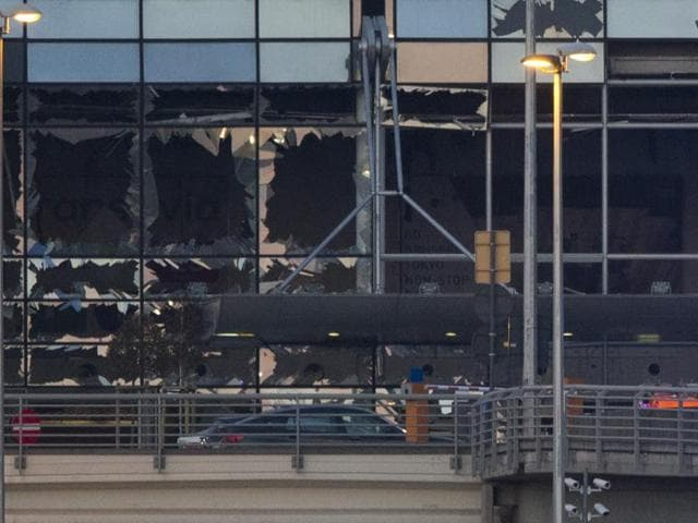 The blown-out facade of the terminal is seen as an ambulance leaves Zaventem Airport, one of the sites of two deadly attacks in Brussels, Belgium.(AP Photo)