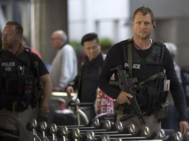 An airport police officer directs a car at the arrivals area of Tom Bradley International Terminal at LAX airport as security is heightened in reaction to bomb attacks in Brussels, Belgium.