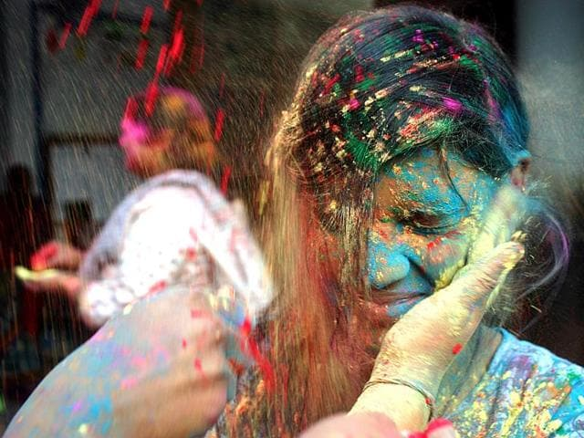Girls playing with gulaal to celebrate Holi