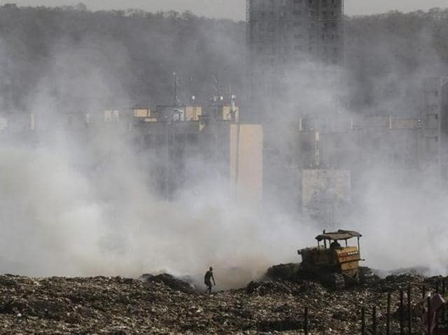 A ragpicker collects recyclable material as smoke billows from the burning garbage at the Deonar dumping ground in Mumbai.