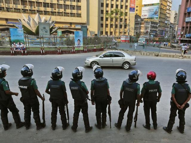 Bangladeshi policemen stand guard on a crossing in Dhaka.