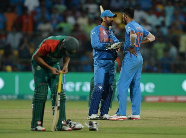 India captain Mahendra Singh Dhoni interacts with Hardik Pandya during the last over of the World T20 cricket match against Bangladesh at the Chinnaswamy Stadium in Bangaluru.