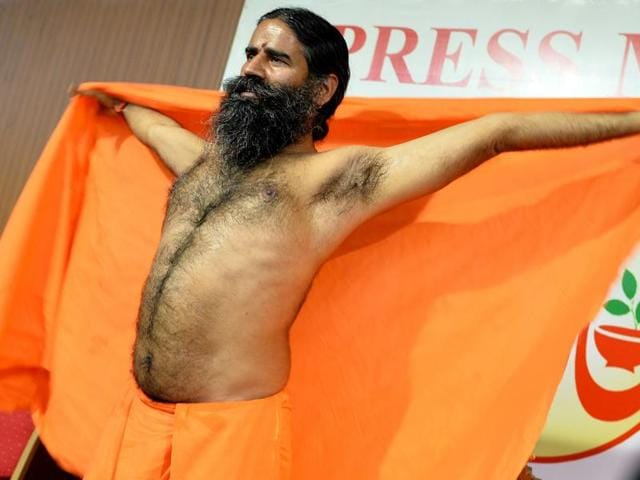 Yoga guru Baba Ramdev stretches after addressing a press conference in Bangalore. (AFP PHOTO)