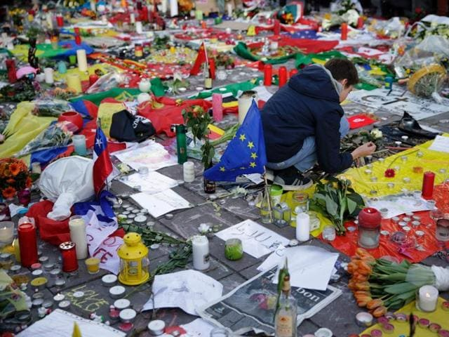 Brussels airport workers and their relatives hold candles as they pay tribute to the victims of Brussels triple attacks near the airport in Zaventem.