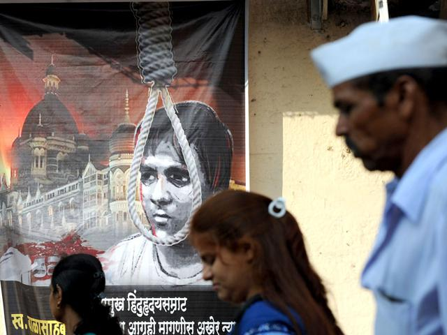 Pedestrians walk past a poster depicting the hanging of Pakistani-born Mohammed Ajmal Kasab.