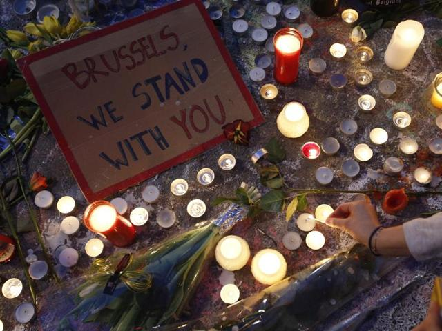 A woman lights a candle among the tributes to the victims of the recent attacks in Brussels, placed in Place de la Bourse in the centre of Brussels, Thursday, March, 24, 2016.