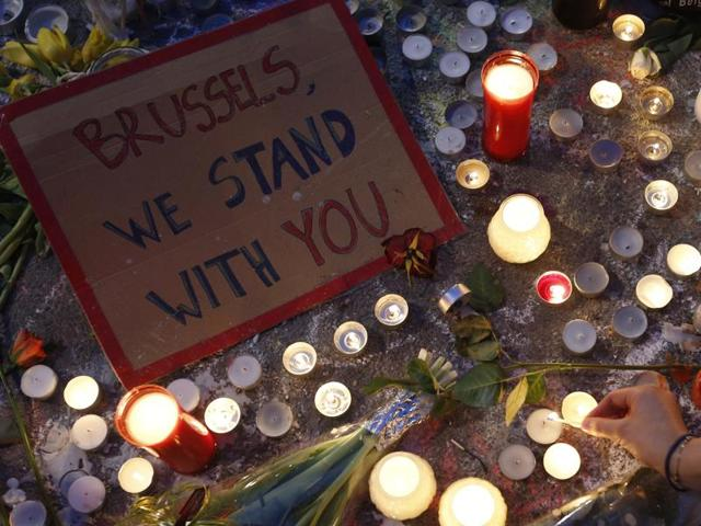 A woman lights a candle among the tributes to the victims of the recent attacks in Brussels.