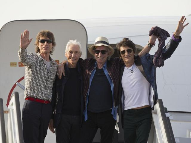 Members of The Rolling Stones, from, Mick Jagger, Charlie Watts, Keith Richards and Ron Wood pose for photos from the plane that brought them to Cuba at Jose Marti international airport in Havana.