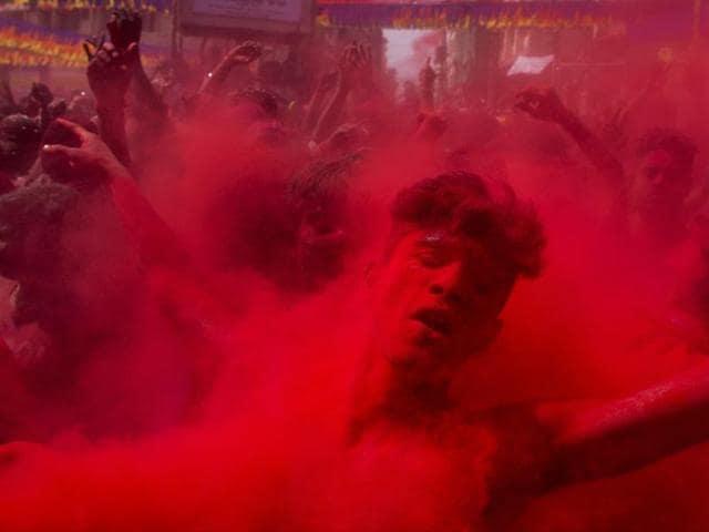 Revellers enjoying rain of coloured water during traditional holi celebration.