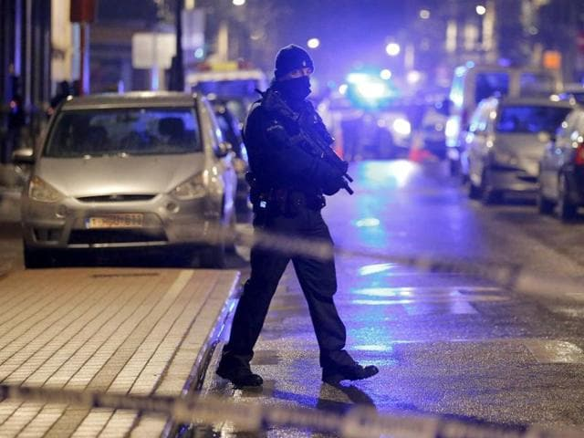A masked Belgian police takes part in police operations in Schaerbeek following Tuesday's bomb attacks in Brussels, Belgium.