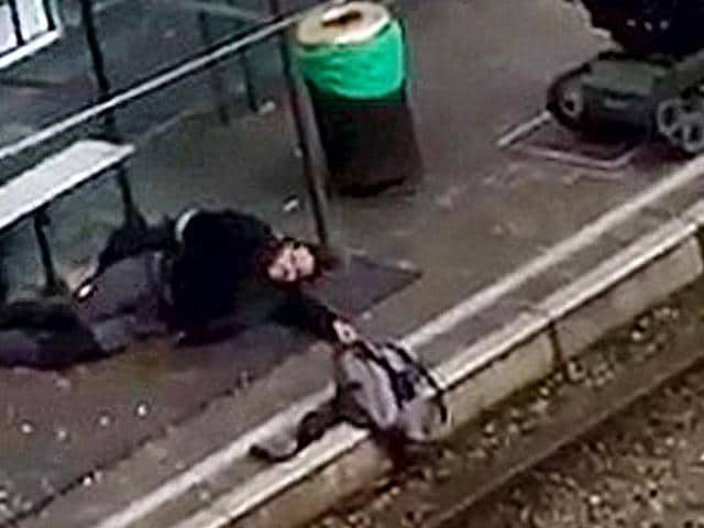 A suspect lies on the platform of a tramway station, in this image taken from amateur video, after he was shot and wounded by police in the Brussels borough of Schaerbeek following Tuesday's bombings in Brussels, Belgium, March 25, 2016.