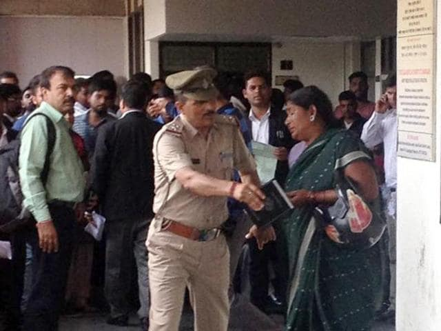 A woman pleading with a police officer to release her husband at the district court complex in Chandigarh on Friday.