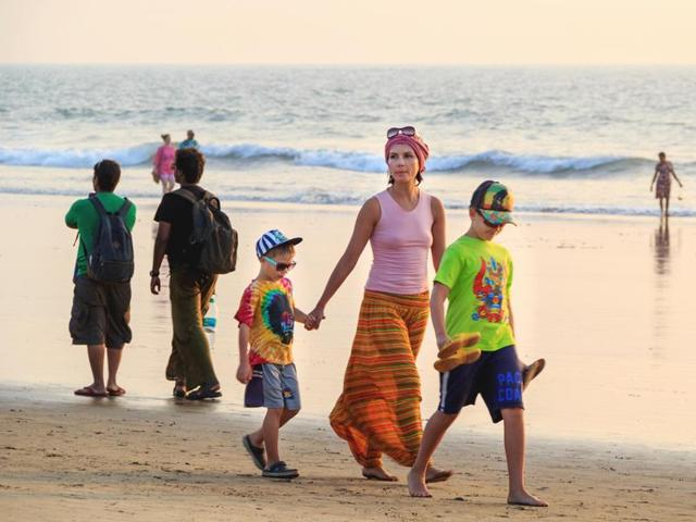 File photo of tourists with backpacks and suitcases walking along the beach on Goa, India.