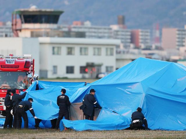 Police inspect a plane crash site covered with a blue sheet at Yao airport in western Japan.