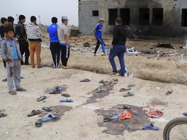 People inspect the aftermath of a suicide bombing at a football field in Iskandariya, Iraq.